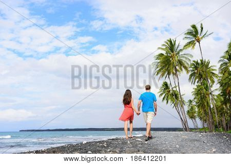 Couple walking on Hawaii secluded black sand volcanic beach on the Big island of Hawaii, hawaiian destination tropical travel for summer vacations. People from behind relaxing on walk.