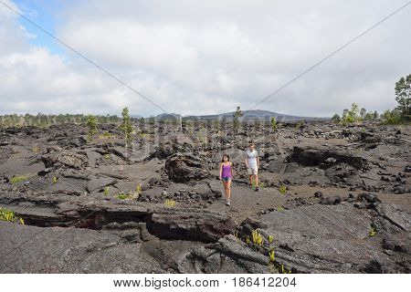 Hawaii destination travelers couple hiking in volcanic rocks on Kilauea volcano in Big island of Hawaii