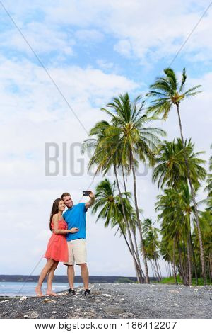 Selfie couple on nature travel Hawaii vacation black sand beach in Big island of Hawaii, USA. Hawaiian holidays getaway. Off the beaten track.
