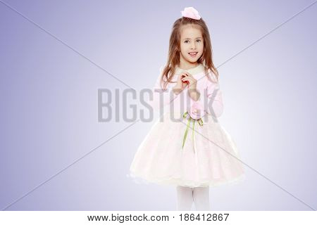 Dressy little girl long blonde hair, beautiful pink dress and a rose in her hair. She folded her arms around her chest.
