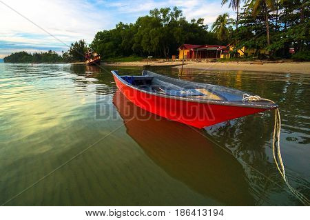 Serene sunrise beach over fishing jetty with fishing boats in fisherman village in Labuan island,Malaysia.