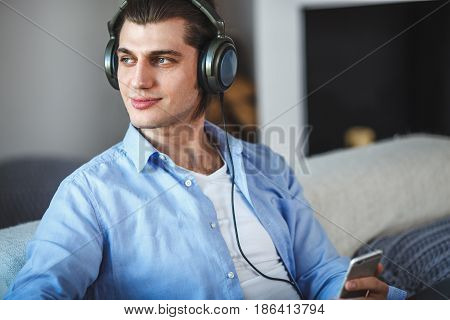 Handsome guy sitting on sofa with headphones and looking to the left side