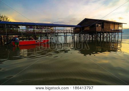 Labuan,Malaysia-May 13,2017:Traditional fisherman with fishing boat during beautiful sun rising sky morning in Labuan island,Malaysia.Aquaculture industry has growth,to contributes the economy of Labuan.