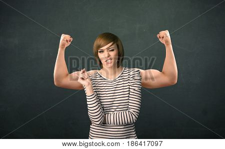 Pretty young woman with strong and muscled arms concept