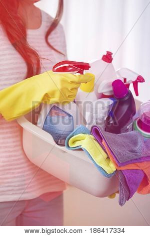Midsection of woman carrying basket of cleaning supplies at home
