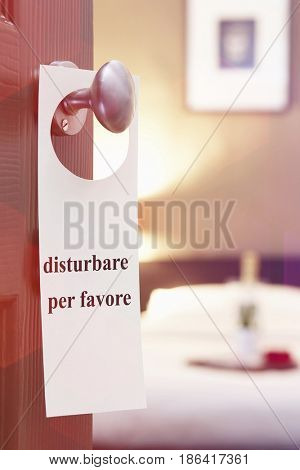 Sign with Italian text hanging on hotel room door