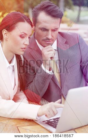Young businesspeople discussing over laptop outdoors
