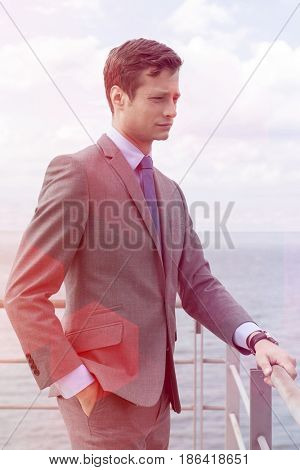 Thoughtful businessman with hand in pocket standing by terrace railings