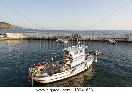 small fishing boats in harbor of agios nicolaos on greek peloponnese with sea and mountains in the background on sunny evening in april