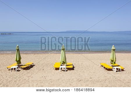 sun chairs wait for people on Stoupa sandy beach in peloponnese on the greek mainland in spring