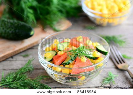 Vegetable salad with cucumbers, tomatoes and corn. Bright, vitamin and yummy salad in a bowl. Healthy vegetable meal. Fork, cucumber, dill on a wooden table. Rustic style