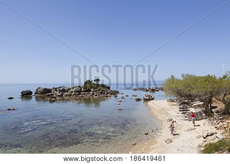 stoupa greece 26 april 2017: mother and daughter on beach of greek village stoupa with blue sea in spring on peloponnese
