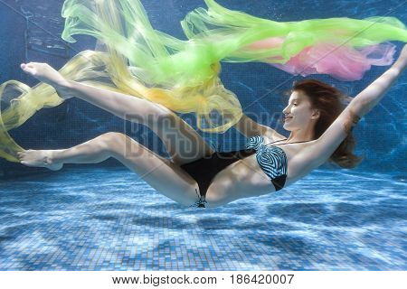 Woman in a swimsuit is playing under the water with a colored fabric.