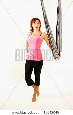 Single calm woman sitting with toes pointed down while doing intense leg stretching exercises wrapped in aerial yoga blanket suspended from ceiling