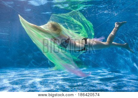 Woman in the water plays with a transparent fabric she dives under the water.