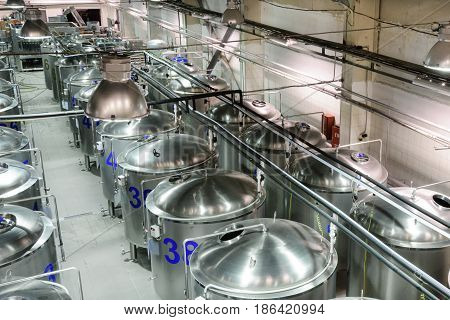 Brilliant metal cisterns lined up in long rows. Modern food production.