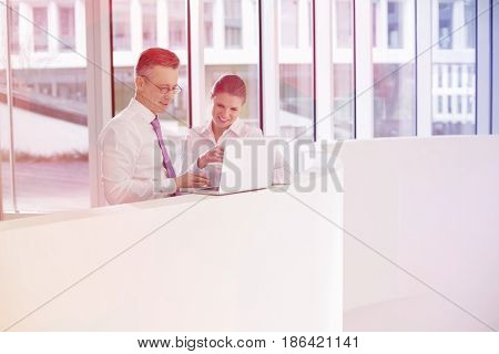 Business people using laptop on railing in office