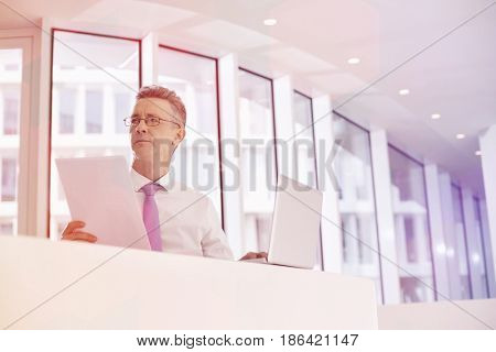 Thoughtful businessman with laptop and documents at railing