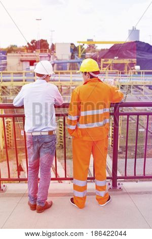 Back view of architects standing against railing at construction site