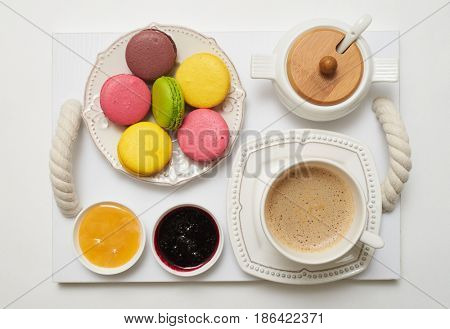 Breakfast with coffee, honey, jam and macaroons on tray on white background