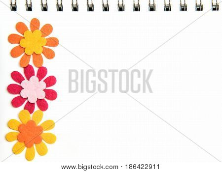 White page of a notebook on a spring with brightly colored flowers and copy space
