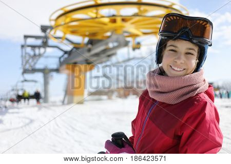 Girl with ski goggles smiles near cableway in ski resort at winter day