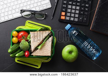 Office desk with supplies and lunch box with vegetables and sandwich. Top view