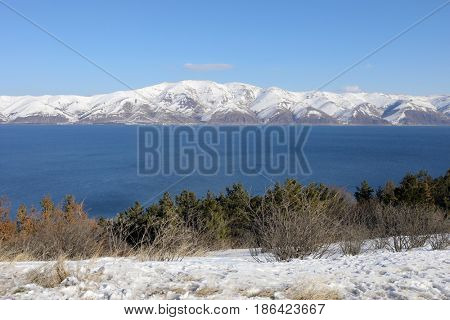 Blue Sevan lake and beautiful snowy mountains at winter sunny day in Armenia