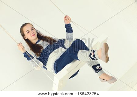 Happy girl teenager in jeans and gaiters swings in white studio and smiles