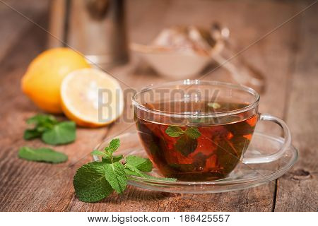 Glass cups of tea with mint on wooden table