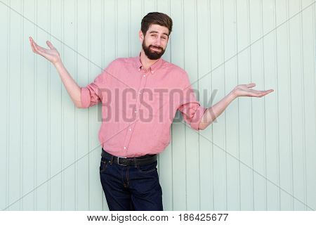 Expressive Young Man Standing With Arms Out To His Side