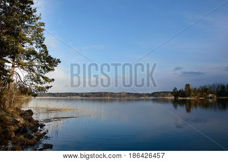 Landscape with view of the lake and rocky shore. Nature is wild Northern and beautiful places. European wildlife lakes and pines.