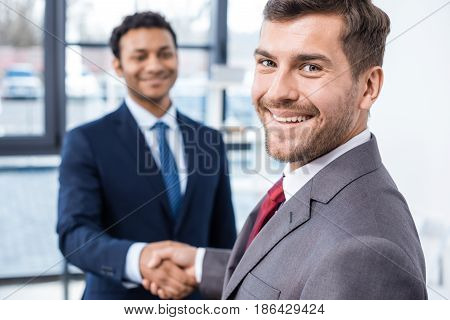 Handsome Young Businessmen Shaking Hands And Smiling At Camera, Business Concept