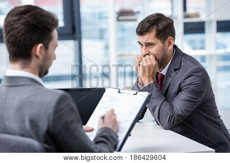 Nervous Man In Formal Wear Looking At Businessman Writing On Clipboard During Job Interview, Busines