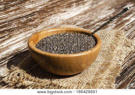 Close up of chia seeds (Salvia hispanica) in wooden bowl on a rustic table. This superfood is a rich in omega-3 fatty acids essential for good health. Healthy eating vegan diet concept.