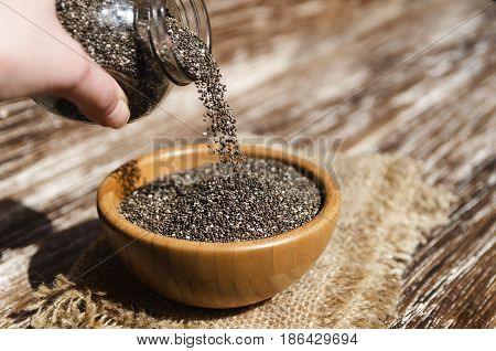 Hand pouring glass jar with chia seeds into wooden bowl. Superfood: Salvia hispanica is a rich in omega-3 fatty acids essential for good health. Healthy eating vegan diet concept.