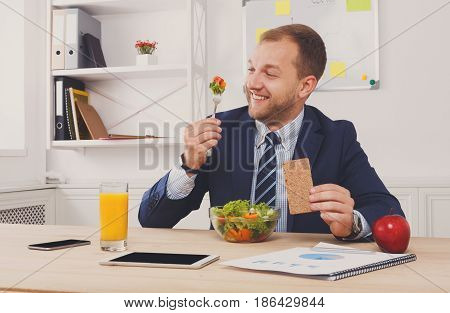 Man has healthy business lunch of vegetable salad in modern office. Young handsome businessman at working place, looking at food, diet and eating right concept.