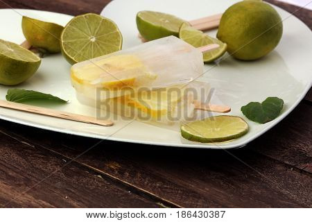 Healthy Lime Mint Popsicles With Fresh Lime Slices On Wooden Background