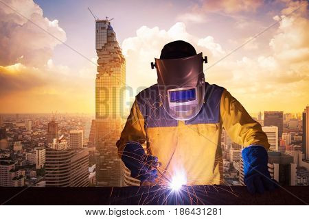 Welding Worker Welding Steel Structure With Modern Building In Big City At Background For Engineerin