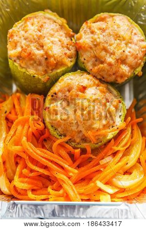 Healthy food delivery, diet concept. Take away of fitness meal. Closeup of stuffed zucchini and carrot salad
