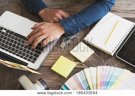 Graphic Designer At Work With Color Samples For Selection. .