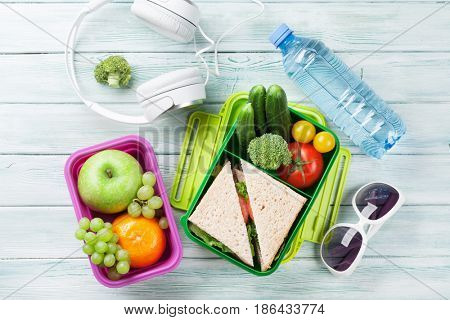 Lunch box with vegetables and sandwich on wooden background. Beach take away food box, headphones and sunglasses. Top view