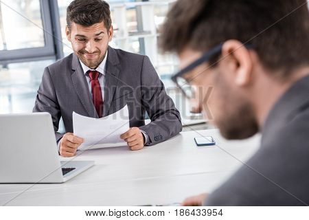 Unsatisfied Boss Analyzing Documents With Colleague Near By At Business Meeting