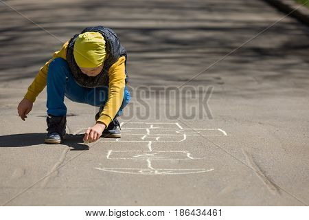 Kid boy drawing hopscotch on asphalt. Child playing hopscotch on playground outdoors on a sunny day. outdoor activities for children.