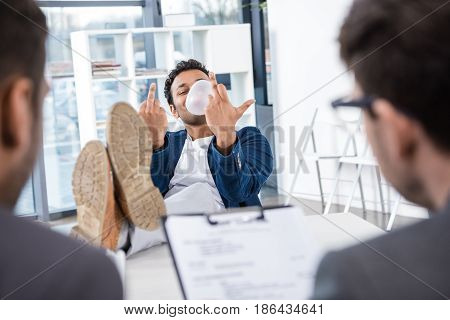 Businessman Blowing Bubble Gum And Showing Middle Fingers During Job Interview, Business Concept