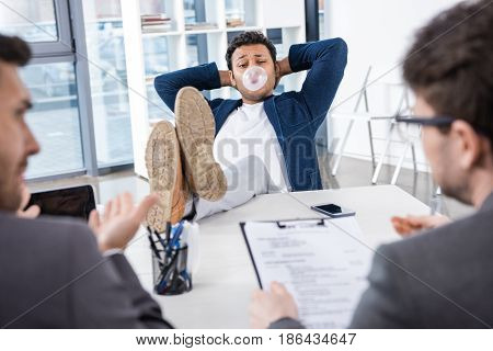 Businessman Blowing Bubble Gum With Legs On Table During Job Interview, Business Concept