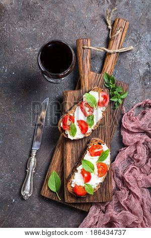 Crostini appetizers with cherry tomatoes, basil, and cheese on dark background, top view on cutting board