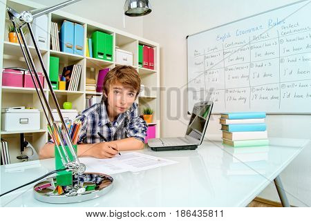 Educational concept. A boy student studying at his workplace with books and laptop.