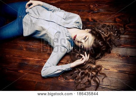 Portrait of a beautiful girl with long curly hair lying on a wooden floor. Youth fashion, beauty. Long hair, haircare.