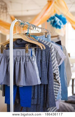 Hangers with clothes for kids on it. Rack with girl's clothes in blue color in a shop